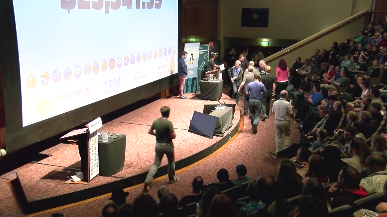 Photo of linux.conf.au attendees coming to the front stage to contribute money towards Outreachy internships