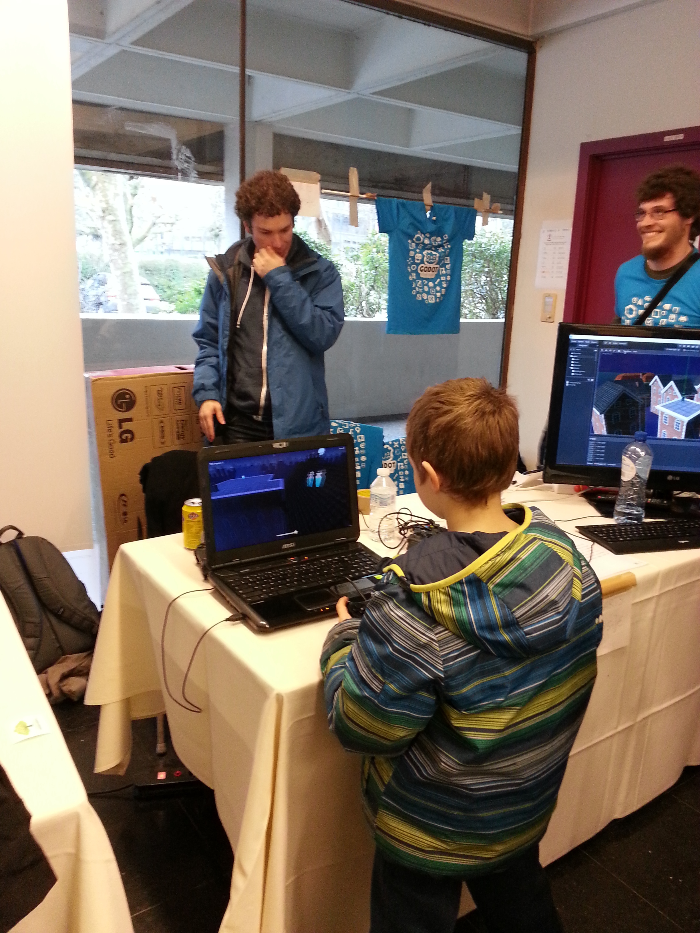 Photo of a child playing a game at Godot's FOSDEM booth