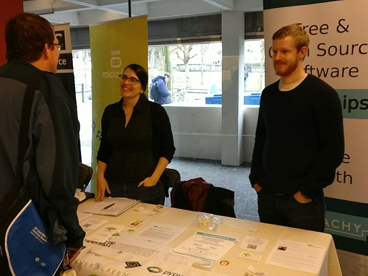 Photo of Conservancy executive director Karen Sandler and Homebrew maintainer Mike McQuaid talking with a visitor at the Conservancy booth at FOSDEM