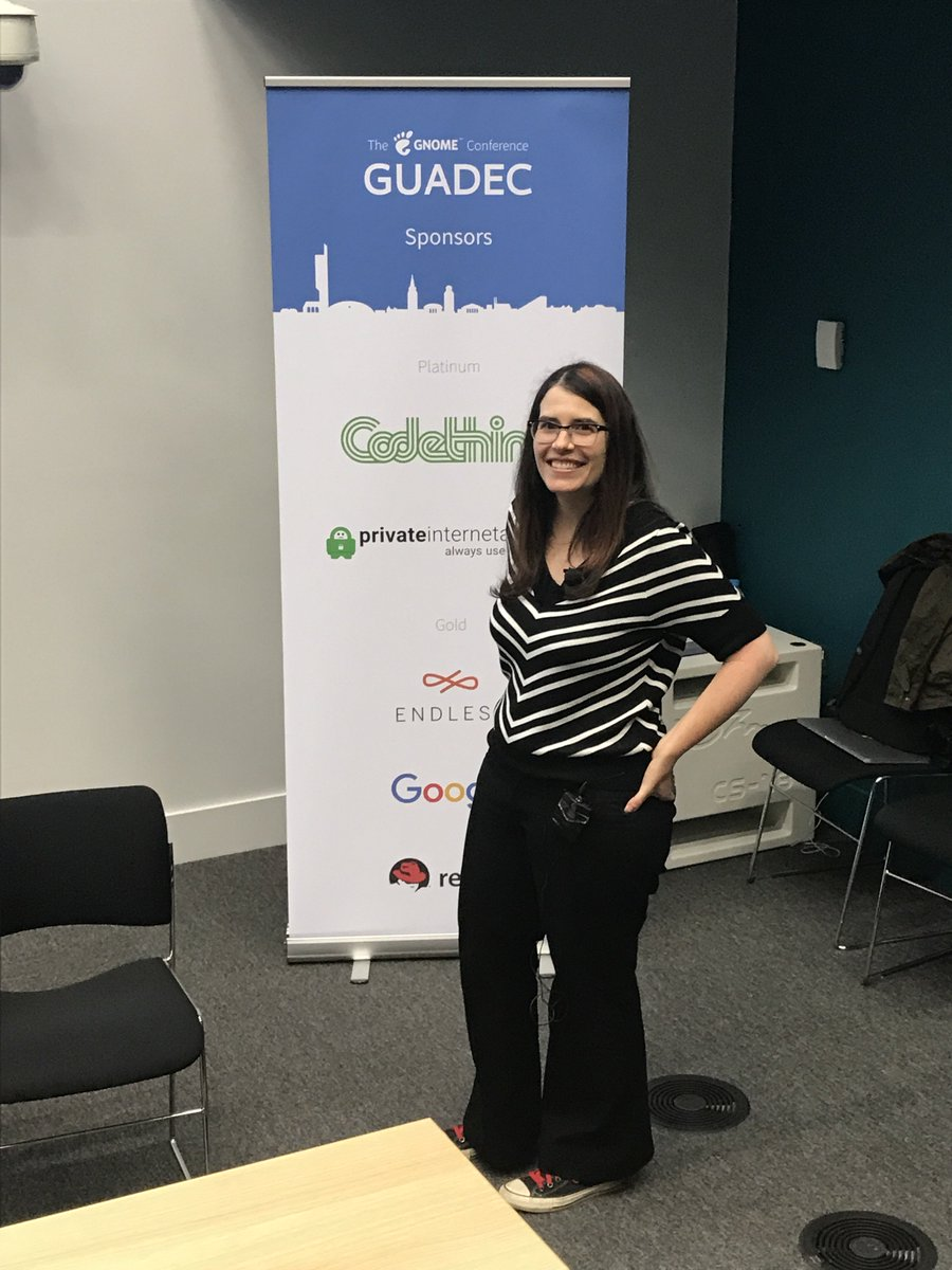 Photo of Karen in front of a banner at GUADEC