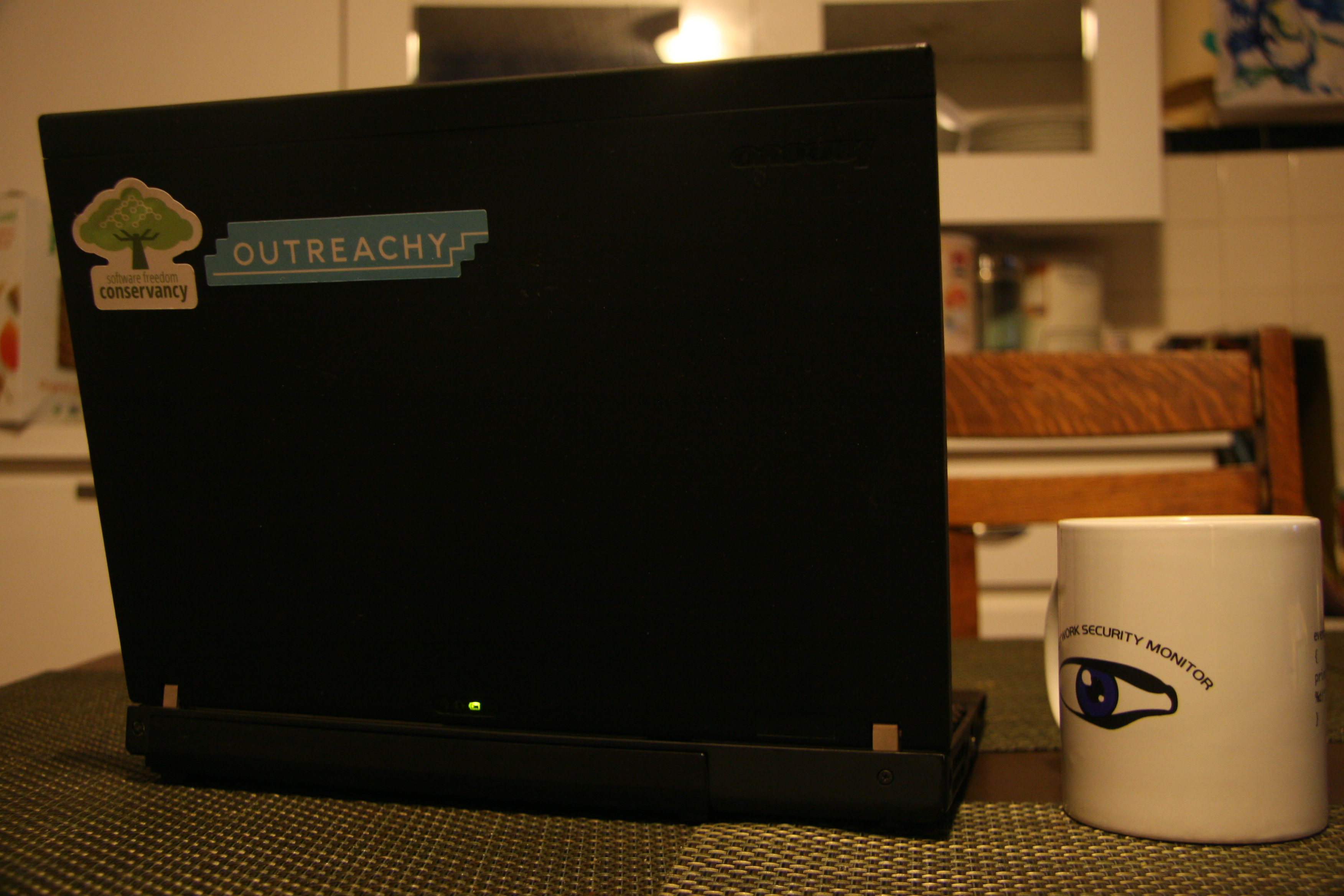 A laptop with Conservancy and Outreachy stickers, alongside a Bro mug